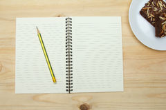 Blank notebook and pencil on wooden table. Top view of blank notebook and pencil on wooden table Stock Photo