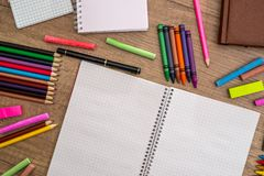 Blank notebook with pencils, chalk colour. On wood table Royalty Free Stock Photos