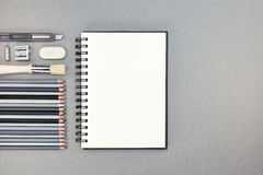 Blank notebook with pencils and other drawing accessories on gra Royalty Free Stock Photo