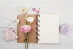 Blank notebook, pink crochet holdel, earphones. Lit candle, flowers, paperweight on wooden background. Copy space Royalty Free Stock Image