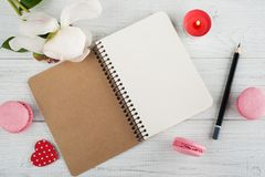 Blank notebook, pink macaroons, lit candle Royalty Free Stock Photo
