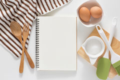 Blank notebook for recipes. Baking ingredients for cooking and blank notebook , wooden cutting board, spoon, egg and sugar for recipes on white background Royalty Free Stock Image