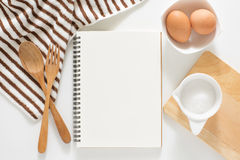 Blank notebook for recipes. Baking ingredients for cooking and blank notebook , wooden cutting board, spoon, egg and sugar for recipes on white background Royalty Free Stock Photography