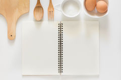 Blank notebook for recipes. Baking ingredients for cooking and blank notebook , wooden cutting board, spoon, egg and sugar for recipes on white background Stock Photo