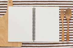 Blank notebook for recipes. Baking ingredients for cooking and blank notebook , wooden cutting board, spoon, egg and sugar for recipes on white background Stock Image