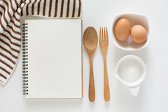 Blank notebook for recipes. Baking ingredients for cooking and blank notebook , wooden cutting board, spoon, egg and sugar for recipes on white background Stock Photography