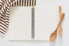 Blank notebook for recipes. Blank notebook and wooden spoon for recipes on white background Royalty Free Stock Photo