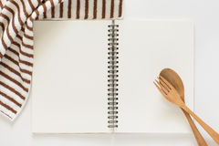 Blank notebook for recipes. Blank notebook and wooden spoon for recipes on white background Stock Images