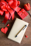 Blank notebook with red gift box and flower on wooden background Royalty Free Stock Photo