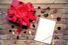 Blank notebook with red gift box on wooden table Royalty Free Stock Images