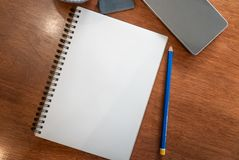 Blank notebook`s page. With pencil and eraser on a wood table royalty free stock images