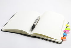 Blank notebook with silver pen. Blank, open lined notepad with ink pen isolated on white background Royalty Free Stock Photos