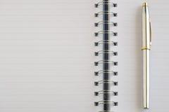 The blank notebook and a silver pen. Stock Photos