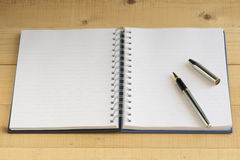 Blank notebook with silver pen. Royalty Free Stock Image