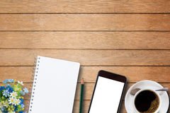 Blank notebook, smart phone and coffee cup on wooden Stock Photos