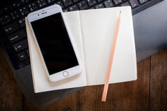 Blank notebook and smartphone with pencil on Laptop Stock Images
