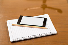 Blank notebook, smartphones and pencil Stock Photography