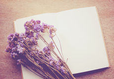 Blank notebook and statice flowers with retro filter effec Stock Photo