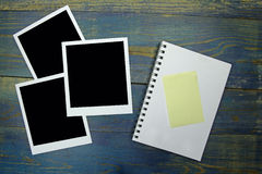 Blank notebook with sticker and photo frame on wooden background Stock Images