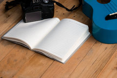 Blank notebook with ukulele guitar and camera Royalty Free Stock Photography