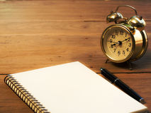 Blank notebook with vintage alarm clock and black pen on wood ta. Ble Royalty Free Stock Photos