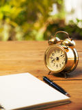 Blank notebook with vintage alarm clock and black pen on wood table. The background is green from tree and light bokeh Stock Photography