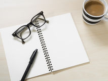 Blank notebook with vintage eyeglasses, pen and cup of hot coffee on wooden table Stock Image