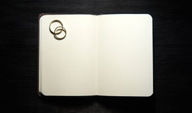 Blank notebook with wedding rings on black background Stock Images