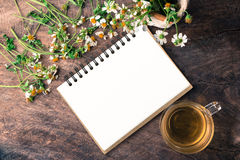 Blank notebook white flower and bas ket of flower and cup of tea on vintage Royalty Free Stock Photo