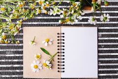 Blank notebook with white flower and bas ket of flower on steel net table Royalty Free Stock Photo