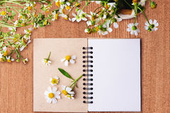 Blank notebook with white flower and bas ket of flower on vintage Royalty Free Stock Photos