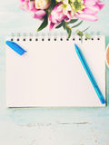 Blank notebook white page with blue pen and flowers Royalty Free Stock Image
