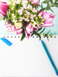 Blank notebook white page with blue pen and flowers. Blank empty notebook page with blue pen. Spring summer flat lay with flowers. Morning wedding planning Royalty Free Stock Photos