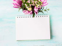 Blank notebook white page with purple pink flowers. Blank empty notebook page. Spring summer flat lay with colorful roses tulips flowers. Morning wedding stock photo