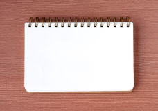 Blank notebook on wood table background, top view Royalty Free Stock Images