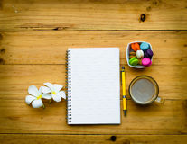 Blank notebook and a yellow pen with hot coffee and colorful swe Royalty Free Stock Images