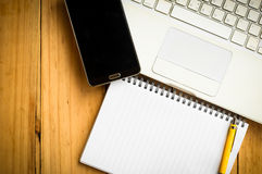 Blank notebook and a yellow pen with mobile phone and laptop on Stock Images