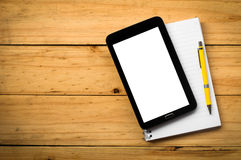 Blank notebook and a yellow pen with mobile phone on  wooden tab Stock Images