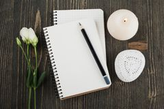 Blank notebooks, lit candle. On wooden background. Copy space Stock Photo