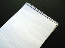 Blank notepad. An angled photo of a blank notepad on a black leather background Stock Photo