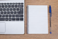 Blank notepad with blue pen next to laptop. Blank notepad with blue pen next to an open laptop Stock Photography