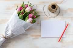Blank notepad and bouquet of tulips wrapped in white paper royalty free stock photography