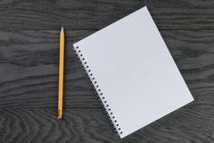 Blank notepad with chequered pages on gray wood Stock Photos