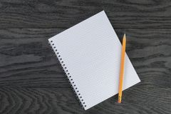 Blank notepad with chequered pages on gray wood Stock Images
