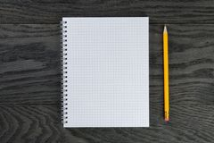 Blank notepad with chequered pages on gray wood Stock Image