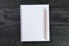 Blank notepad with chequered pages on gray wood Royalty Free Stock Photo
