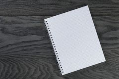 Blank notepad with chequered pages on gray wood Stock Photography