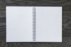 Blank notepad with chequered pages on gray wood Royalty Free Stock Images