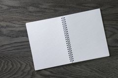 Blank notepad with chequered pages on gray wood Royalty Free Stock Photos