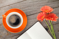 Blank notepad, coffee cup and orange gerbera flowers Royalty Free Stock Photo